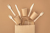 Zero waste, plastic free concept. Paper bag with disposable paper cups, plate, wooden forks and knives on beige background. Eco sustainable living