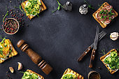 Background of cooking Italian bruschetta. Frame made of sandwiches with avocado salami and cucumber. Menu concept top view