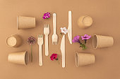 Zero waste plastic free concept Disposable paper cups with wooden forks and knives on beige background Eco sustainable living