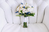 Stylish wedding bouquet with white roses lies on the background of a light gray sofa. Wedding details and decorations. Flowers for the bride.
