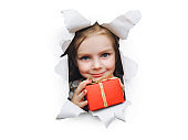 A fanny little smiling girl looks out of a hole in white pastel paper and holds a red box with a gift in her hand. Christmas and New Year concept and birthday concept. Copy space.