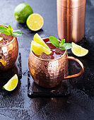 Cold Moscow Mules cocktail with ginger beer, vodka, lime and mint. Grey stone background.