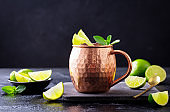 Moscow Mule cocktail with ginger beer, vodka, lime and mint. Dark background. Close up.
