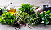 Assortment of fresh herbs, olive oil and spices. Wooden background. Close up.