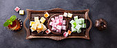 Assortment of Turkish delights on a copper tray with glass of tea. Grey background. Top view.