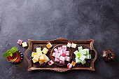 Assortment of Turkish delights on a copper tray with glass of tea. Grey background. Copy space. Top view.