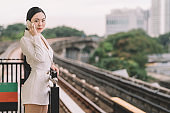 an asian chinese female young businesswoman on the move in monorail train station waiting for train listening to smart phone