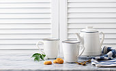 Tea in mugs with teapot on marble background. Copy space.