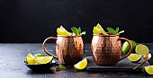 Moscow Mules cocktail with ginger beer, vodka, lime and mint. Grey background. Copy space.