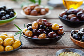 Assortment of fresh olives on a plate with olive tree brunches. Wooden background. Close up.