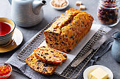 Fruit cake Bara Brith with cup of tea. Welsh traditional dessert. Grey background. Close up.