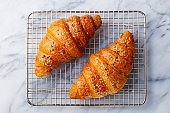 Croissants on cooling rack. Traditional French food. Marble background. Close up. Top view.