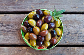 Assortment of fresh olives on a plate. Wooden background. Close up. Top view.