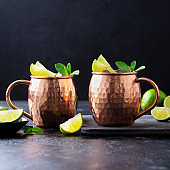 Moscow Mules cocktail with ginger beer, vodka, lime and mint. Dark background. Close up.
