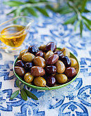Assortment of fresh olives on a plate with olive tree brunches. Blue textile background.