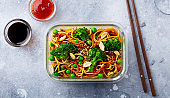 Stir fry noodles, udon with vegetables in lunch box. Grey background. Close up. Top view.