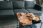 pizza, bread , chicken pieces and spaghetti on table in living room ready to eat