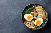 Asian noodle soup, ramen with chicken, tofu, vegetables and egg in black bowl. Slate background. Copy space. Top view.