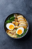 Asian noodle soup, ramen with chicken, tofu, vegetables and egg in black bowl. Slate background. Top view.