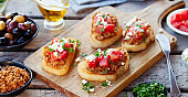 Bruschetta with olive tapenade and fresh tomatoes on cutting board. Wooden background. Close up.