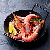 Prawns with lemon and fresh herbs in a black frying pan. Stone background. Close up.