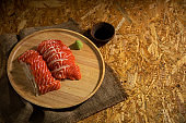 Sliced salmon placing on wooden plate together wasabi radish and shoyu on burlap table by top view with copy space