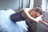 Young ballet dancer lying on crossbar in studio active lifestyle