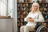 Senior woman with disability recovery at home wheelchair holding cup