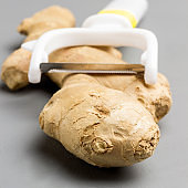 Fresh ginger root and peeler on gray background,