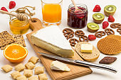 Balanced protein breakfast. Brie cheese on cutting board. Cookies, fruits and berries, orange juice