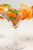 Wine glass with shrimp and herbs.
