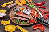 Sliced grilled marbled beef steak in plate. Vegetables on table.
