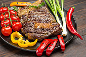 Grilled Marbled beef steak medium rare with vegetables on black plate.