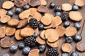 Blueberries and blackberries and chocolate pancakes. Dark wood background.