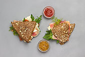 Whole wheat sandwiches with sesame seeds and ham.