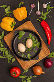 Two eggs in a pan. Tomatoes, yellow and red peppers, garlic, spinach on black background