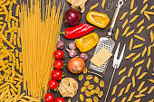 Organic food on black background. Variety of types and shapes of dry Italian pasta with vegetables