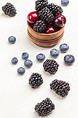 Blackberry and cherry in wooden box. Blueberries and blackberries on table.