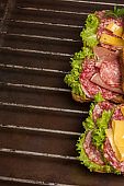Grilled sandwiches with salami, cheese and salad on metal grill with copy space
