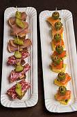 Assortment of canapes with salmon, bacon, cheese, pickles on white plate