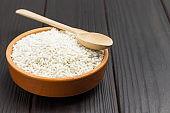 White rice in ceramic bowl and wooden spoon on top.
