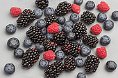 Berries: blackberry, blueberry and raspberry on gray background.