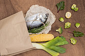 Food set. Paper bag with raw fish and vegetables.
