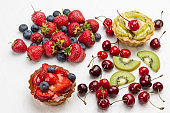 Tarts decorated with fresh berries. Strawberry and blueberries, Kiwi and red cherry on white
