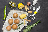 Raw potatoes and one peeled potato on white paper with rosemary,