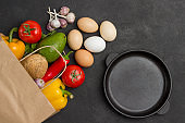 Set of products for diet food. Brown paper bag with vegetables, frying pan and eggs