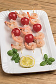 Shrimps with cucumber and tomatoes on skewer in white plate.