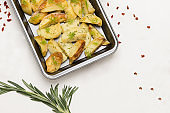 Baked potatoes in baking dish. Rosemary and peppers on table.
