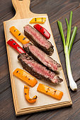 Grilled beef steak, cut into pieces on cutting board with red and yellow pepper.