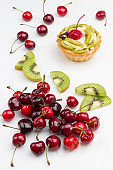 Tart decorated with red cherry and kiwi.  Kiwi and red cherry on white background.